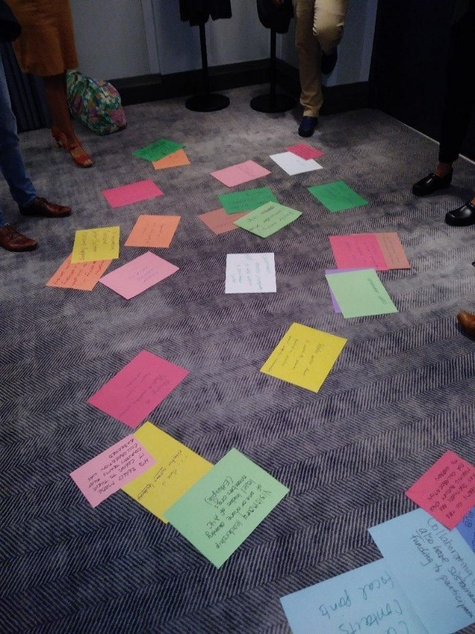 A bunch of colorful papers scattered over a grey carpet. Each paper has writing in English on it.